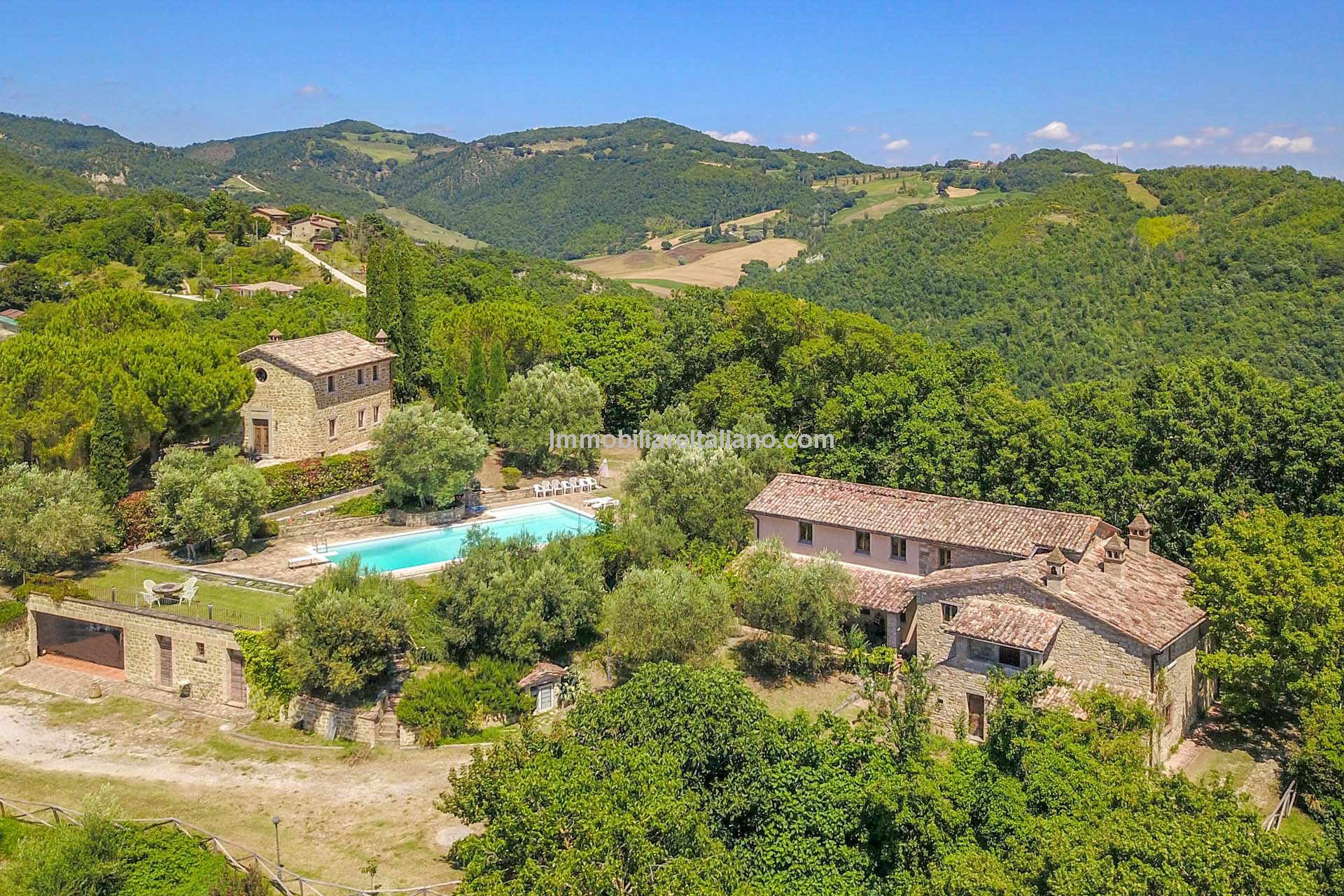 Aerial view of farhouse and coverted chapel for sale with pool