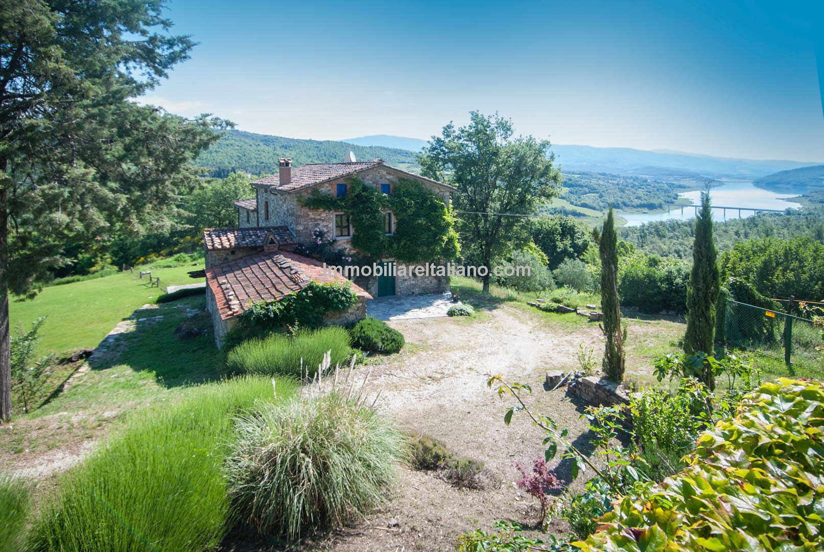 A pair of farmhouses for sale in Tuscany near Caprese Michelangelo overlooking Lake Montedoglio, available for sale together or separately. The villa farmhouse has 5 bedrooms and the larger farmhouse has 6 bedrooms.