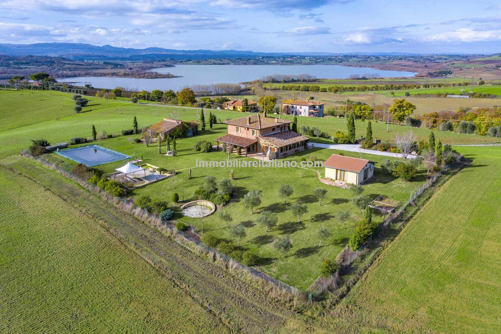 Aerial view of Farmhouse, annexes, swimming pool and gardens with Lake Trasimeno in the background